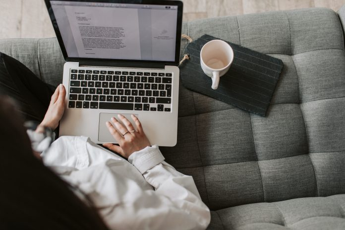 Woman sitting on a couch writing a marketing strategy, copywriting